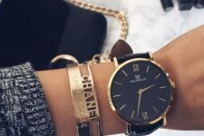 15 a large black and gold watch and gold bracelets to highlight it