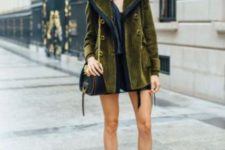 15 an olive green short coat with large buttons, a black crossbody and burnt orange velvet boots