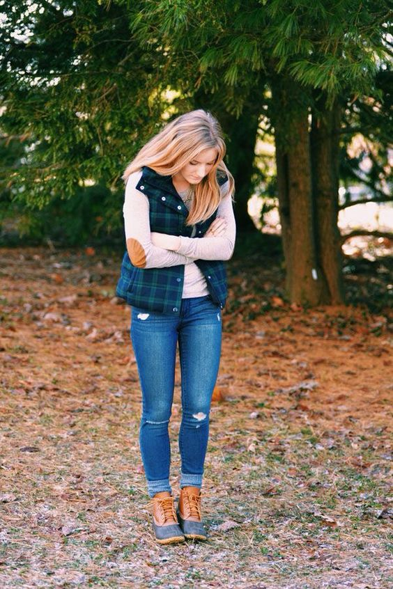 ripped jeans, a neutral sweater, a plaid quilted vest and comfy boots