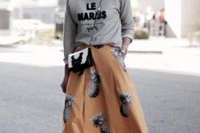 16 a grey sweatshirt, a yellow midi skirt with a pineapple print and white chucks