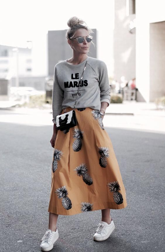 a grey sweatshirt, a yellow midi skirt with a pineapple print and white chucks