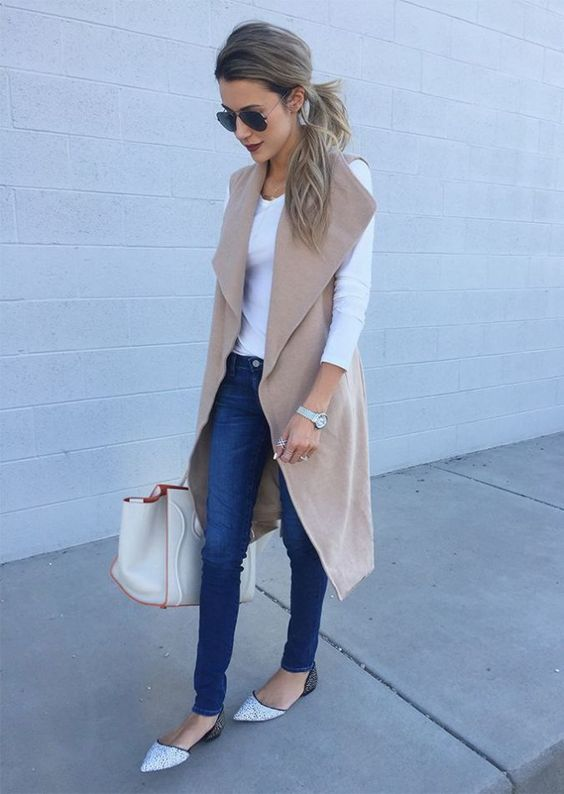 blue skinnies, a white top, a beige sleeveless coat and silver and black flats