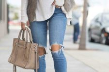 16 ripped blue jeans, a white sweater, a faux fur vest, grey booties and a blush bag