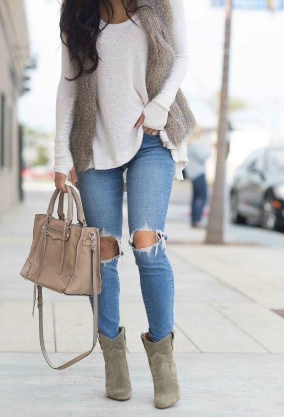 ripped blue jeans, a white sweater, a faux fur vest, grey booties and a blush bag
