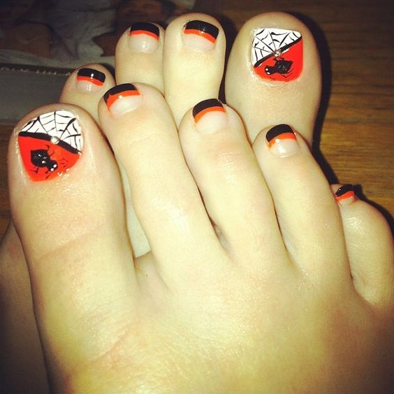 striped orange and black nails and accent nails with rhinestones and spiders