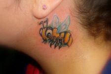 Cartoon bee tattoo behind the ear