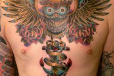 Colorful owl and anchor tattoo on the chest