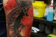 Eagle, clock and red flowers tattoo on the hand