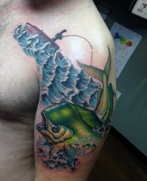 Green fish tattoo on the arm
