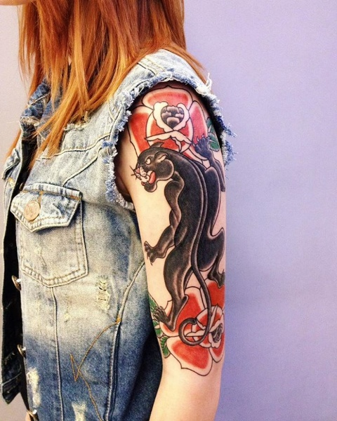 Half-sleeve panther and red flowers tattoo