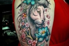 Lion with blue flowers tattoo on the arm