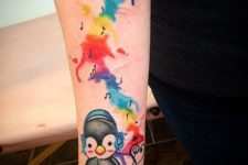 Musical penguin tattoo on the forearm