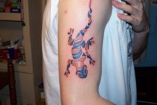 Orange and blue tattoo on the arm