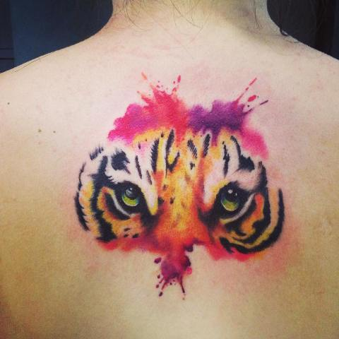 Pink, purple and yellow tattoo on the back