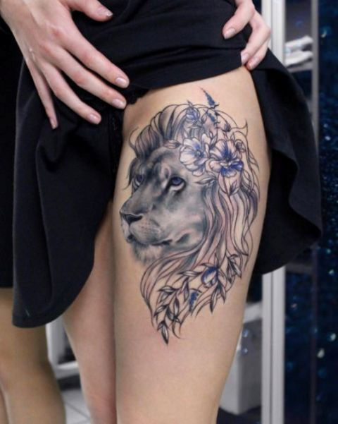 Pretty lion with lilac flowers tattoo on the thigh