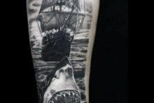 Shark and ship tattoo on the arm