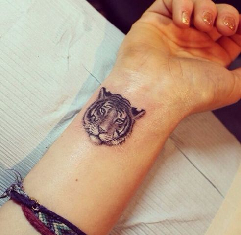 Small tiger head tattoo on the wrist