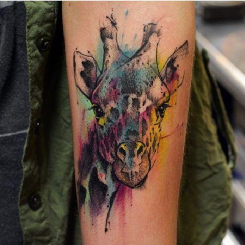 Watercolor giraffe tattoo on the arm