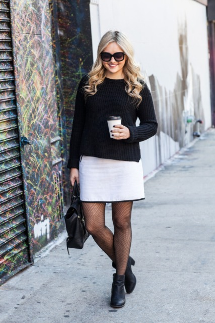 With black shirt, white skirt and black ankle boots