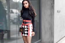 With printed leather skirt, black turtleneck, white boots and mini bag