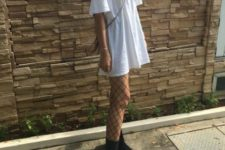 With white oversized t-shirt, black boots and mini bag