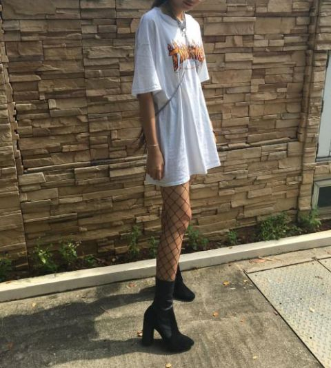 With white oversized t shirt, black boots and mini bag