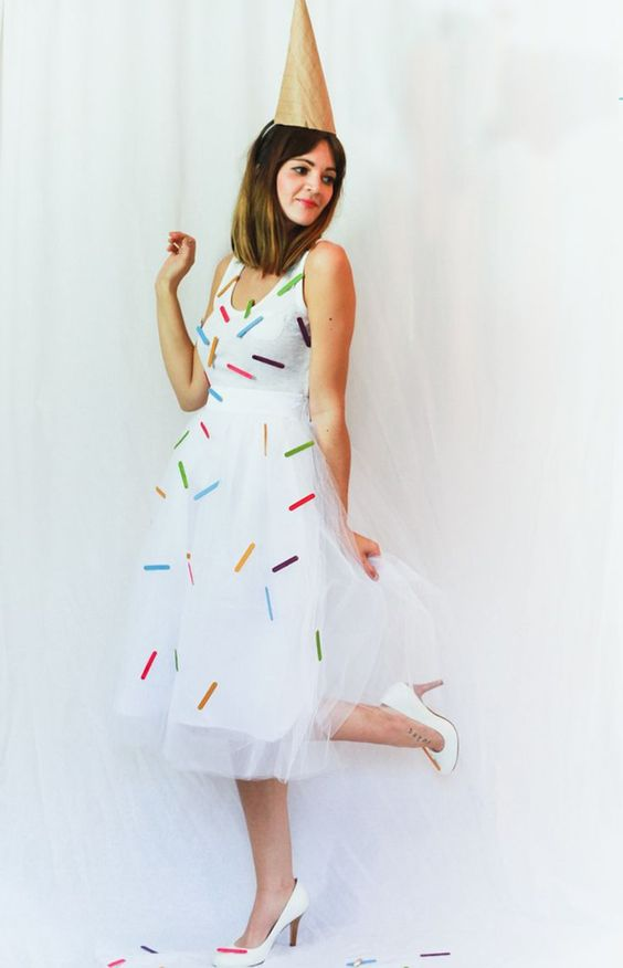 an ice cream cone costume of a flowy white sleeveless dress with cofetti attaached, white shoes and a cone hat