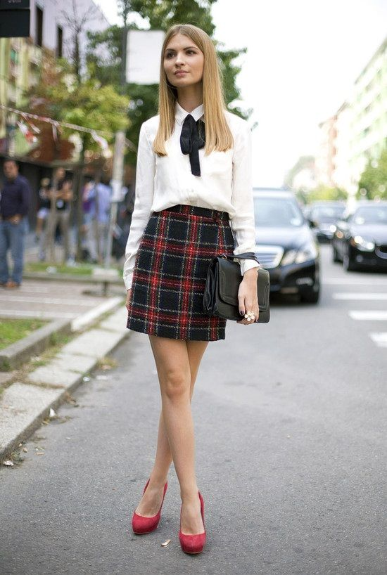 a plaid skirt, a white shirt with a velvet bow, red suede shoes and a black bag