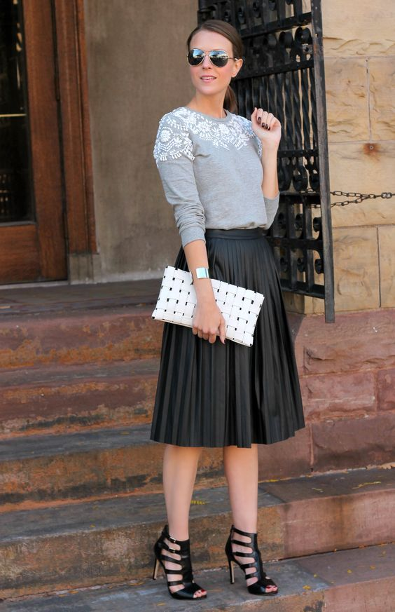 strappy black heels, a black leather plated skirt, a grey embellished sweater