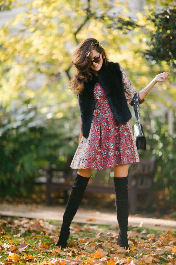a colorful print dress, a black faux fur vest, black suede tall boots