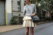 05 a layered pleated skirt, a grey embellished sweater, black shoes and a large bag