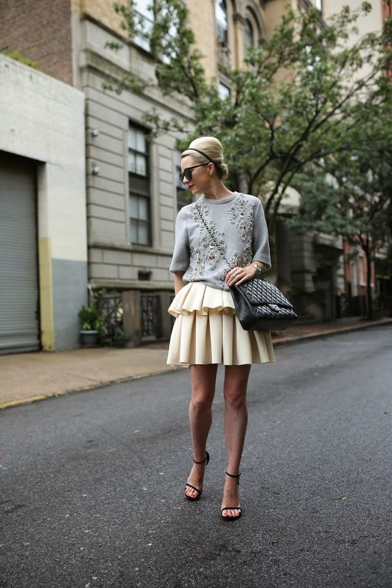 a layered pleated skirt, a grey embellished sweater, black shoes and a large bag