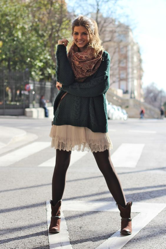 a white lace dress, a dark green oversized sweater, a scarf, black tights and brown boots
