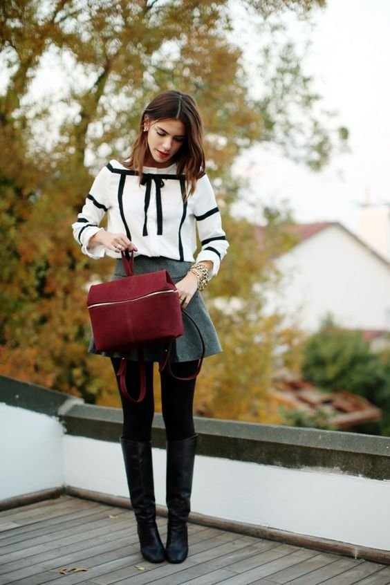 a grey A line skirt, a white shirt with black ribbon, black tights, black tall boots and a red suede bag