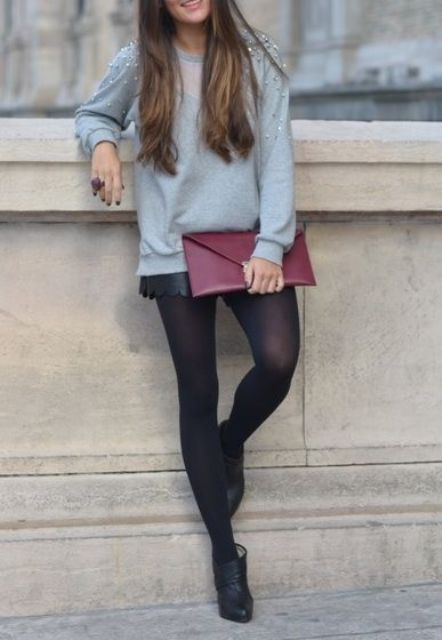 an embellised grey sweater, black leather shorts, tights and booties