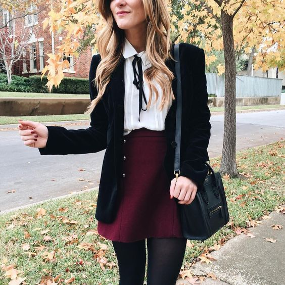 a burgundy mini skirt, a white shirt with a black bow, a black velvet blazer and tights