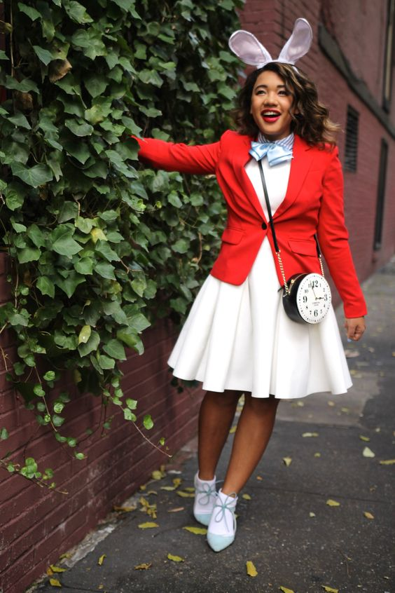 bunny costume from Alice In Wonderland with a white dress, a red blazer, dusty blue shoes with socks, a clock  crossbody and ears