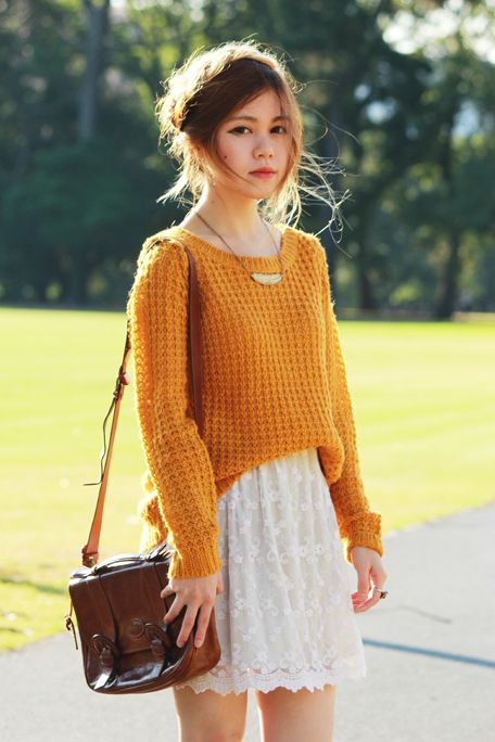 Picture Of an orange sweater over a white lace dress and a brown ...