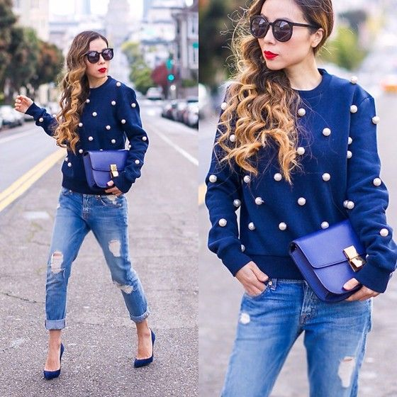 blue cuffed jeans, navy suede heels, a navy sweatshirt with large pearls and a matching bag