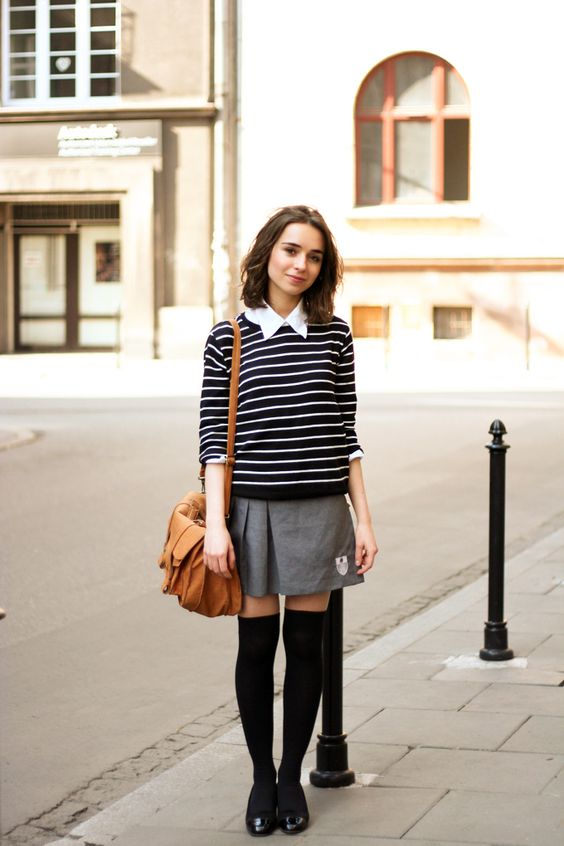 a grey pleated skirt, a striped sweater over the shirt, black stockings and flats