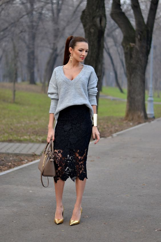a black lace midi pencil skirt, a slouchy green sweater with a deep V-neckline, metallic shoes and a brown bag