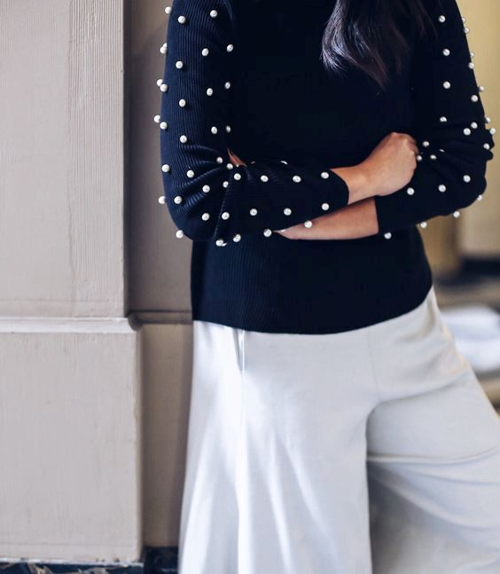 a navy sweater contrasts large white pearls on the sleeves and neutral culottes