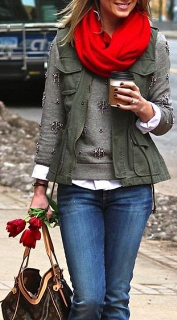 blue jeans, a white shirt, a grey sweater, an olive green vest and a red scarf