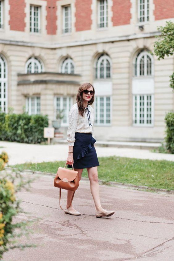 neutral flats, a polka dot shirt with a ribbon bow, a black skirt with a ruffle