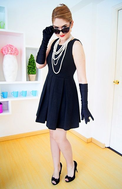 a stylish Audrey Hepburn costume with a sleeveless black dress, black gloves, black shoes and pearl strands