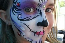15 half face bold paint with purple, black and white touches and rhinestones for a cool look
