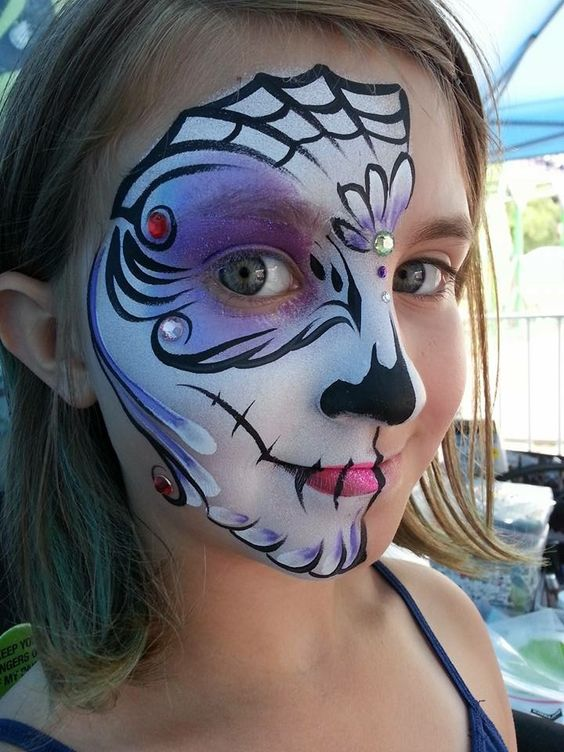 half face bold paint with purple, black and white touches and rhinestones for a cool look