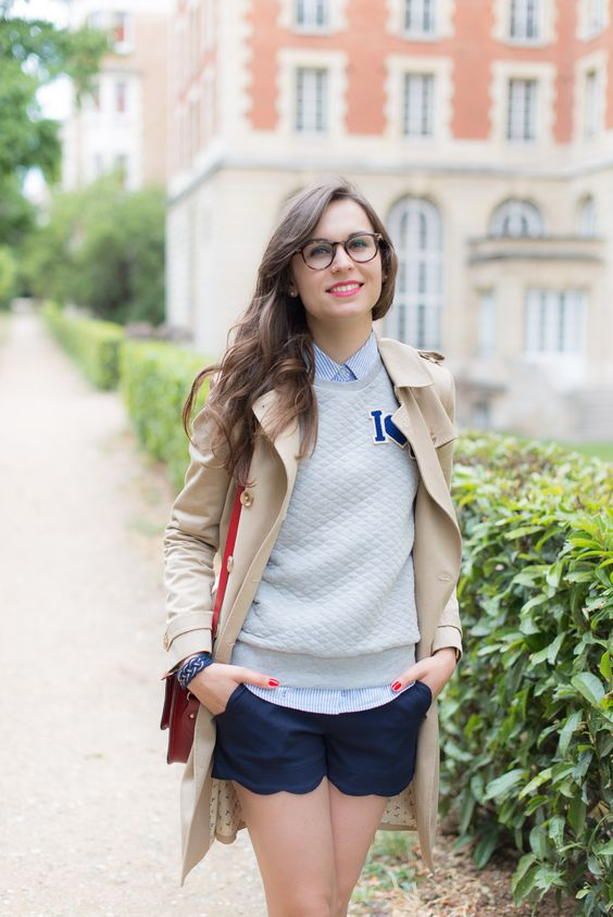 navy scallop shorts, a neutral sweater over a blue striped shirt and a beige trench