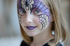 16 purple Halloween kid's face paint with spider webs and a spider for a bold look