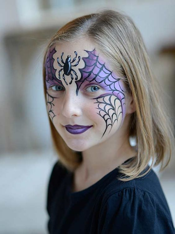 purple Halloween kid's face paint with spider webs and a spider for a bold look